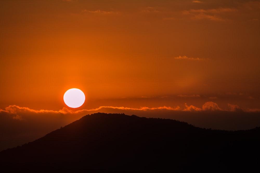 silhouette of mountain under golden sun