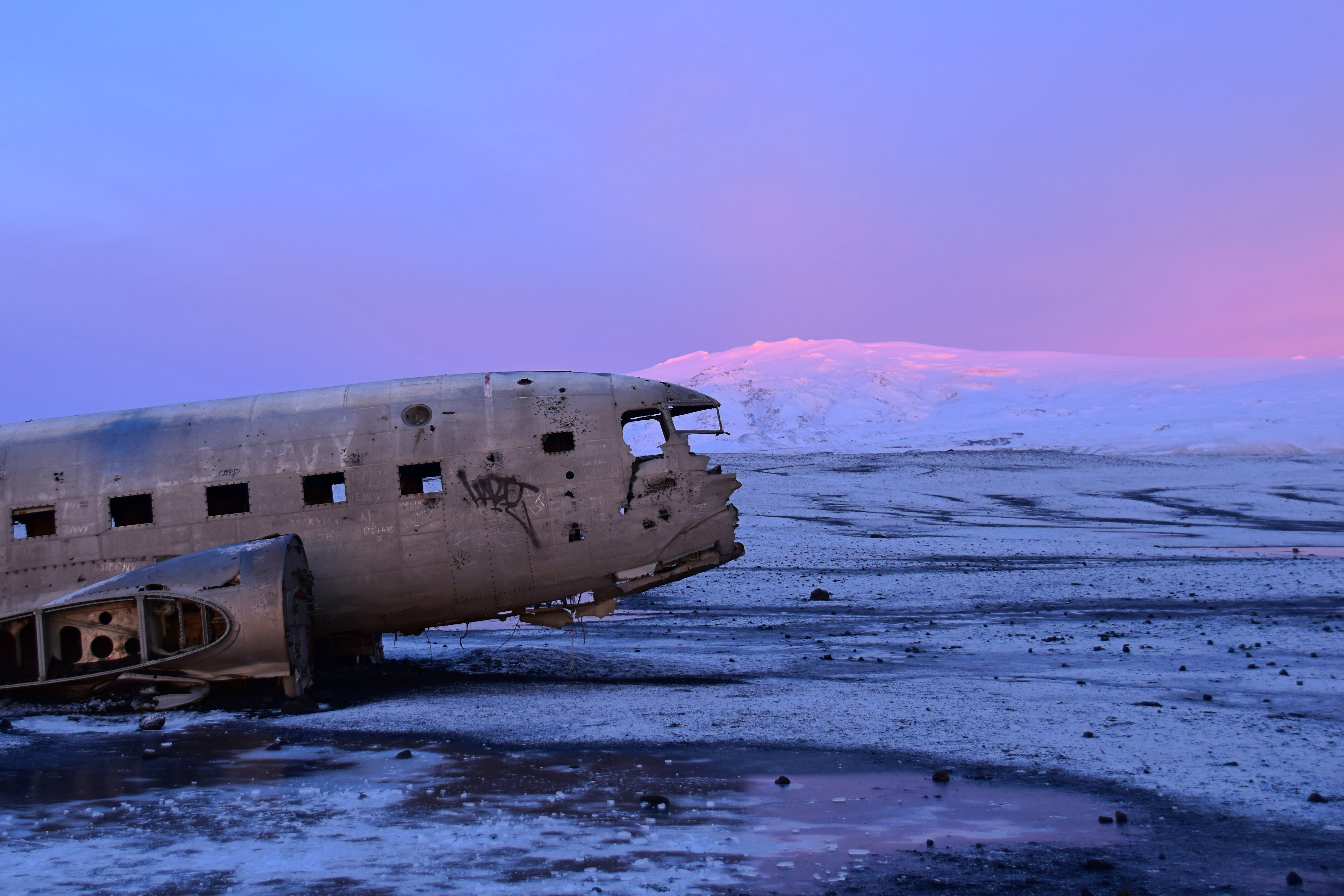 gray wrecked air plane on snow field