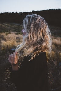woman holding hair in grass field