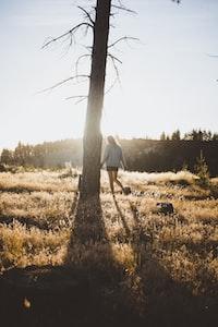 woman walking around tree during daytime