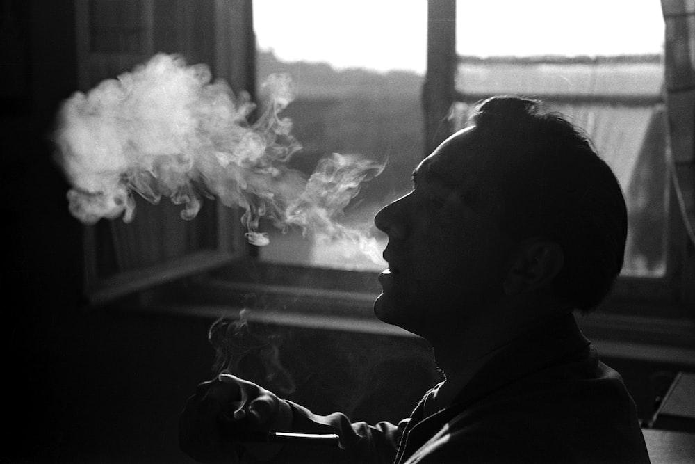 person smoking beside window