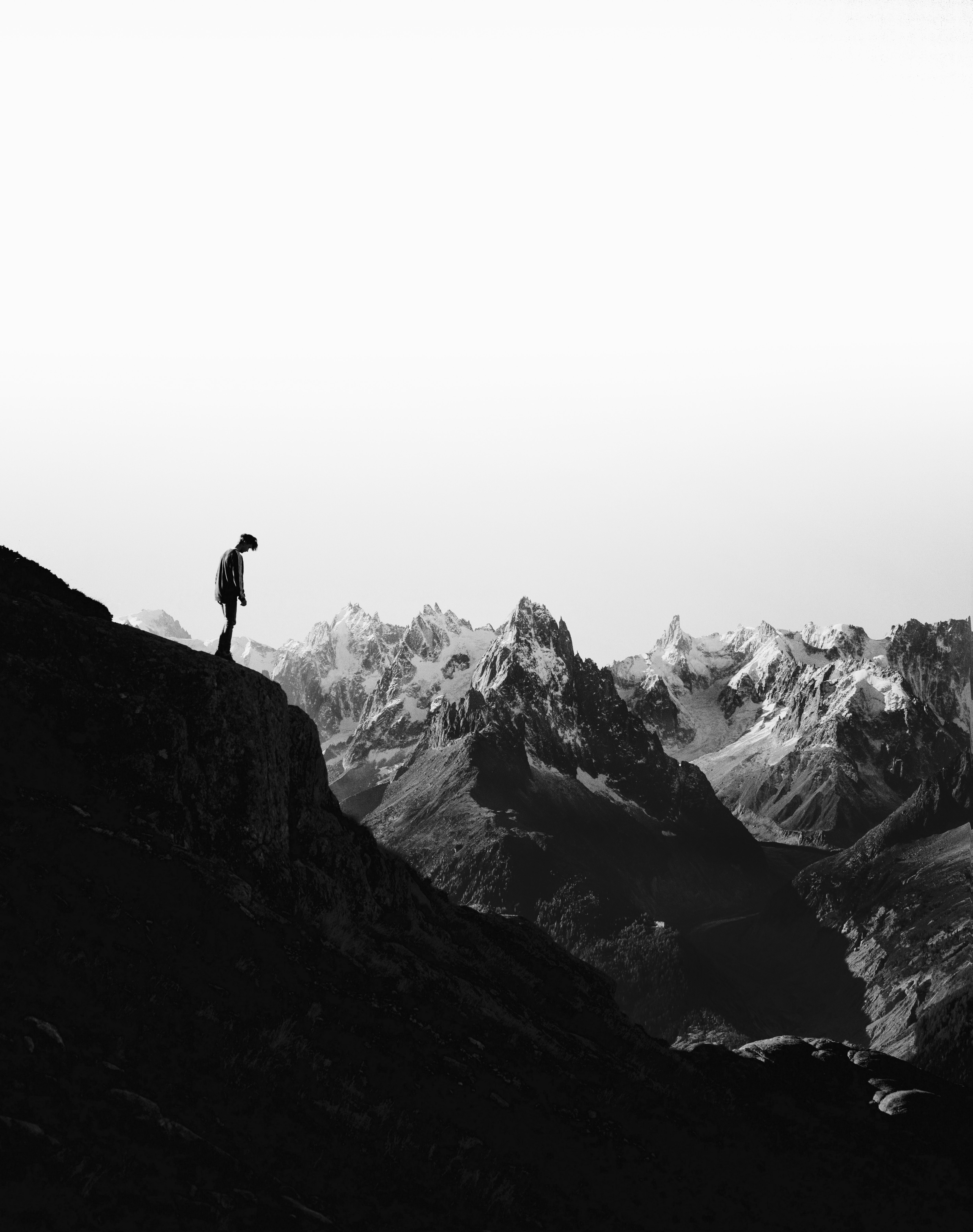 silhouette of person standing on cliff in front of snowed mountains