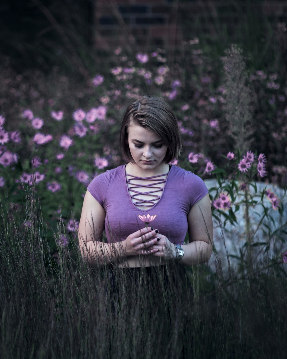 selective focus photo of woman standing on green and pink flower field at daytime