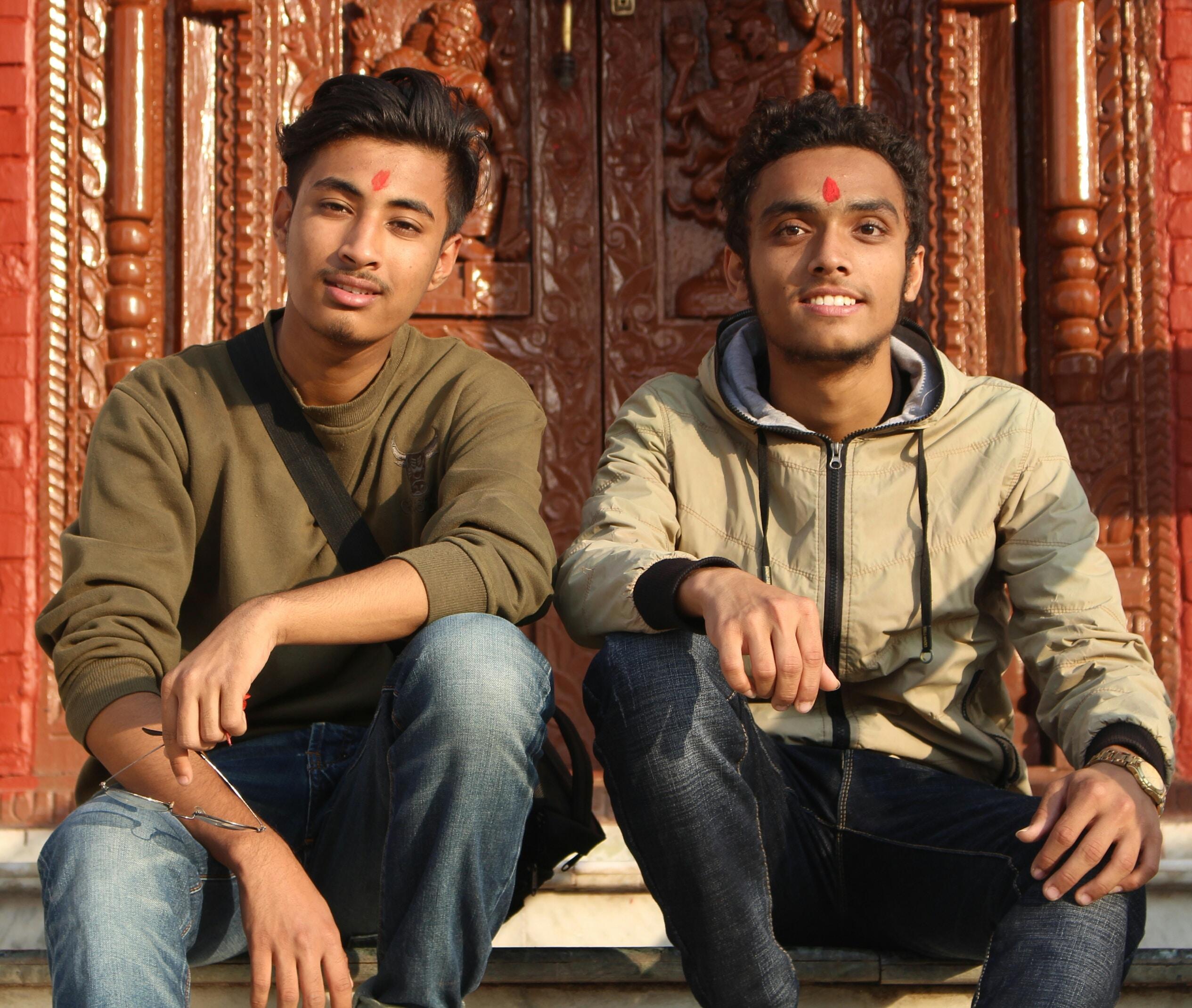 man in brown sweatshirt sitting beside man in brown hoodie near closed brown door