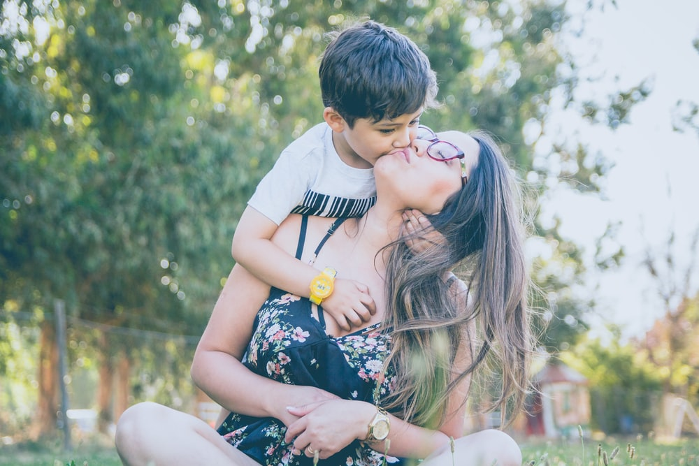 woman sitting on ground while boy standing on her back kissing her at daytime