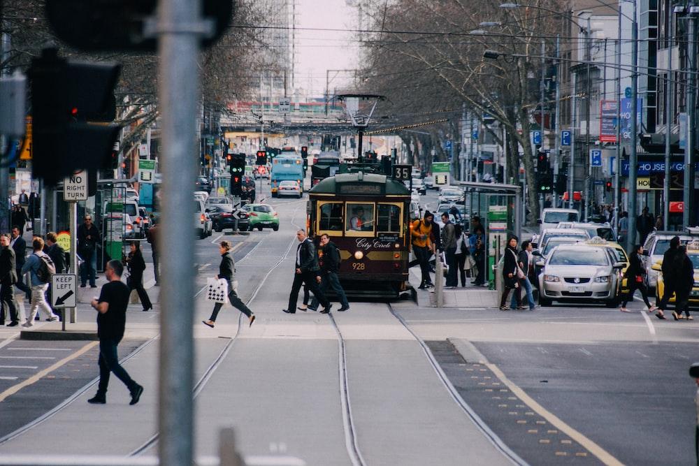 people crossing road near yellow train