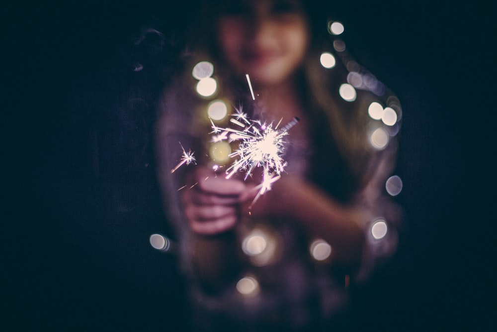 bokeh photography of woman holding sparkler
