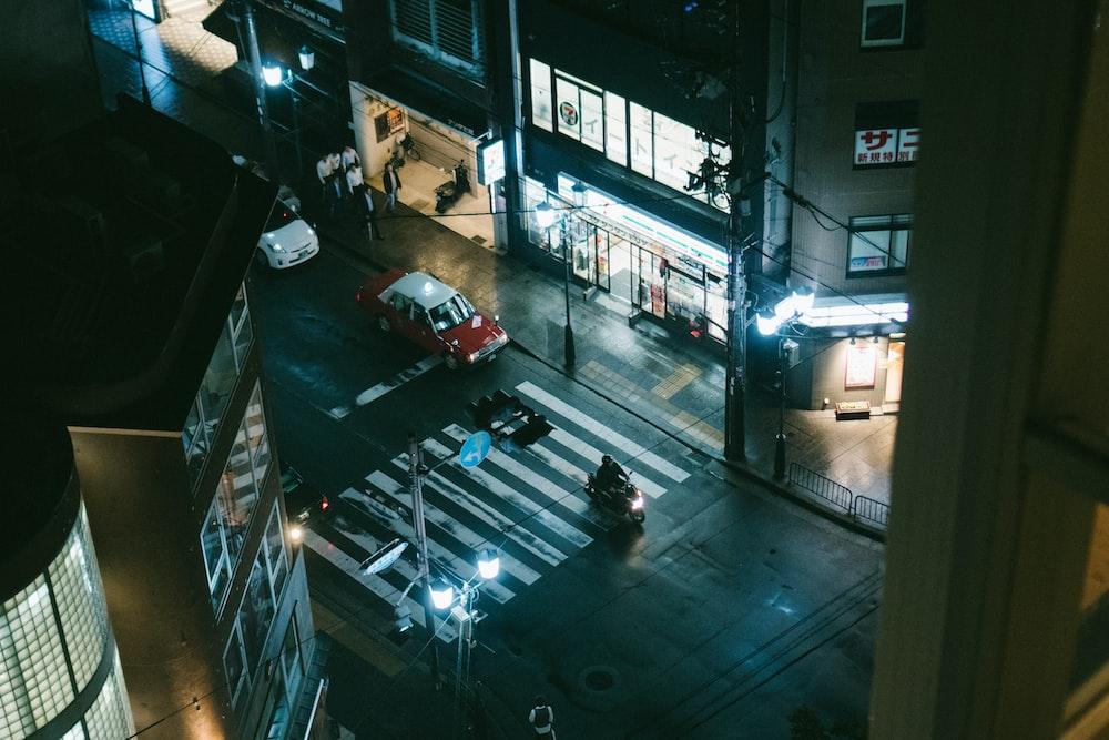 man riding motorcycle on road pedestrian lane during nighttime