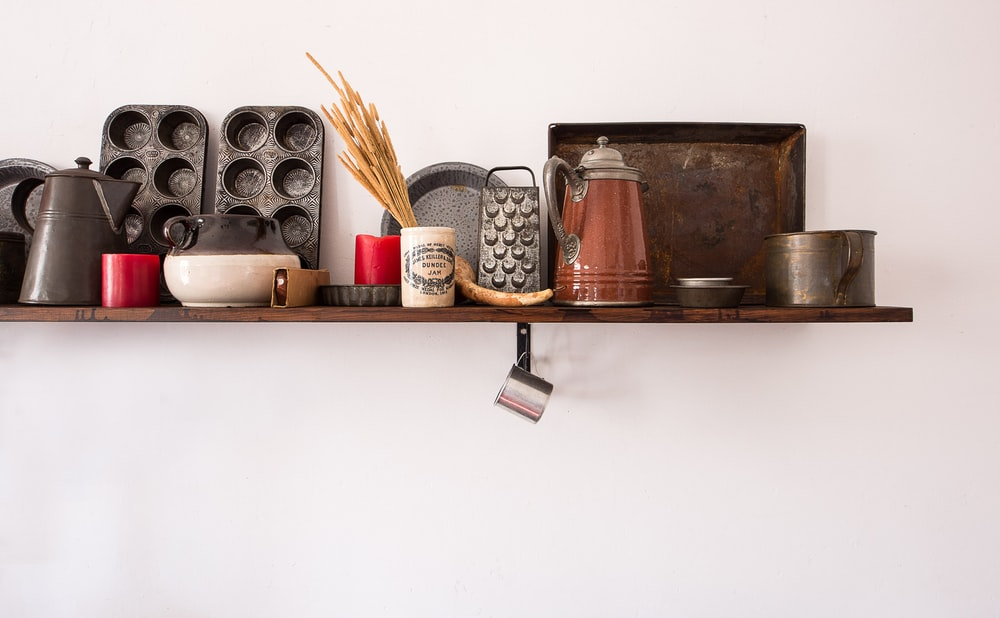 kitchen utensil lot on brown wooden floating shelf