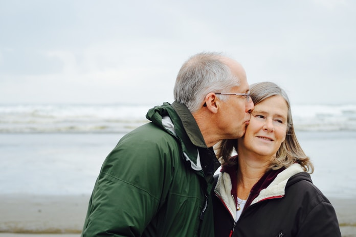 man kissing woman on check beside body of water