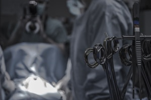 gray surgical scissors near doctors in operating room