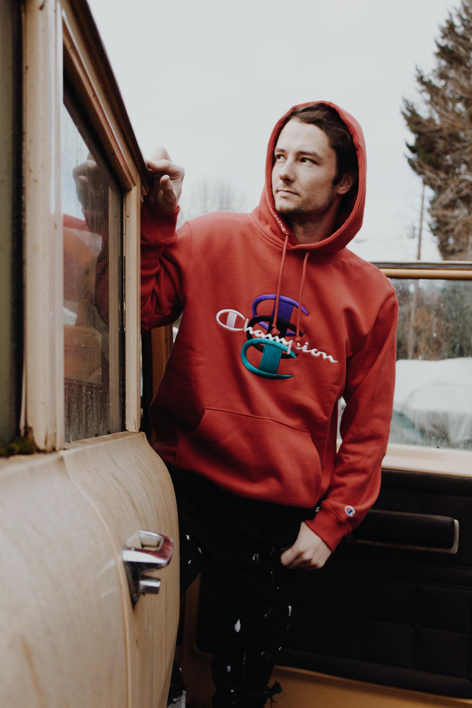 man wearing red Champion brand hoodie