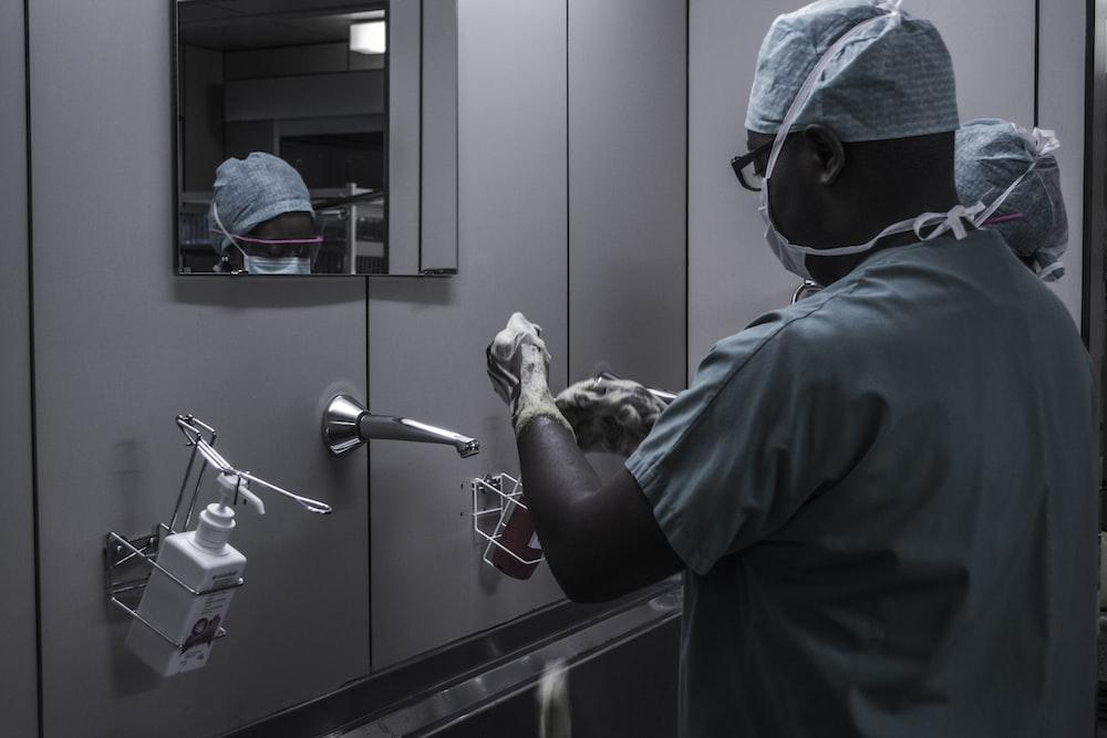man wearing surgical suit near mirror