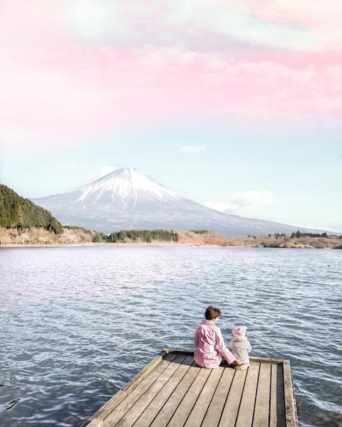 two children sitting on dock
