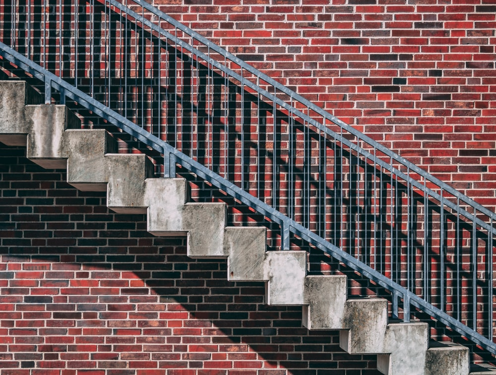 gray metal stair beside red brick wall