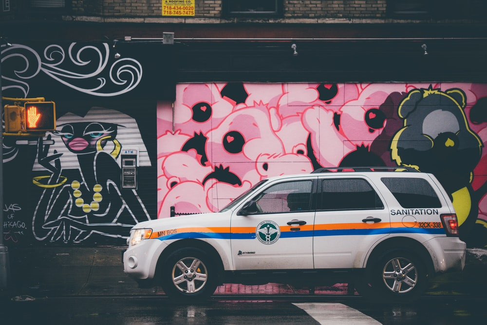 white SUV parking near graffiti wall