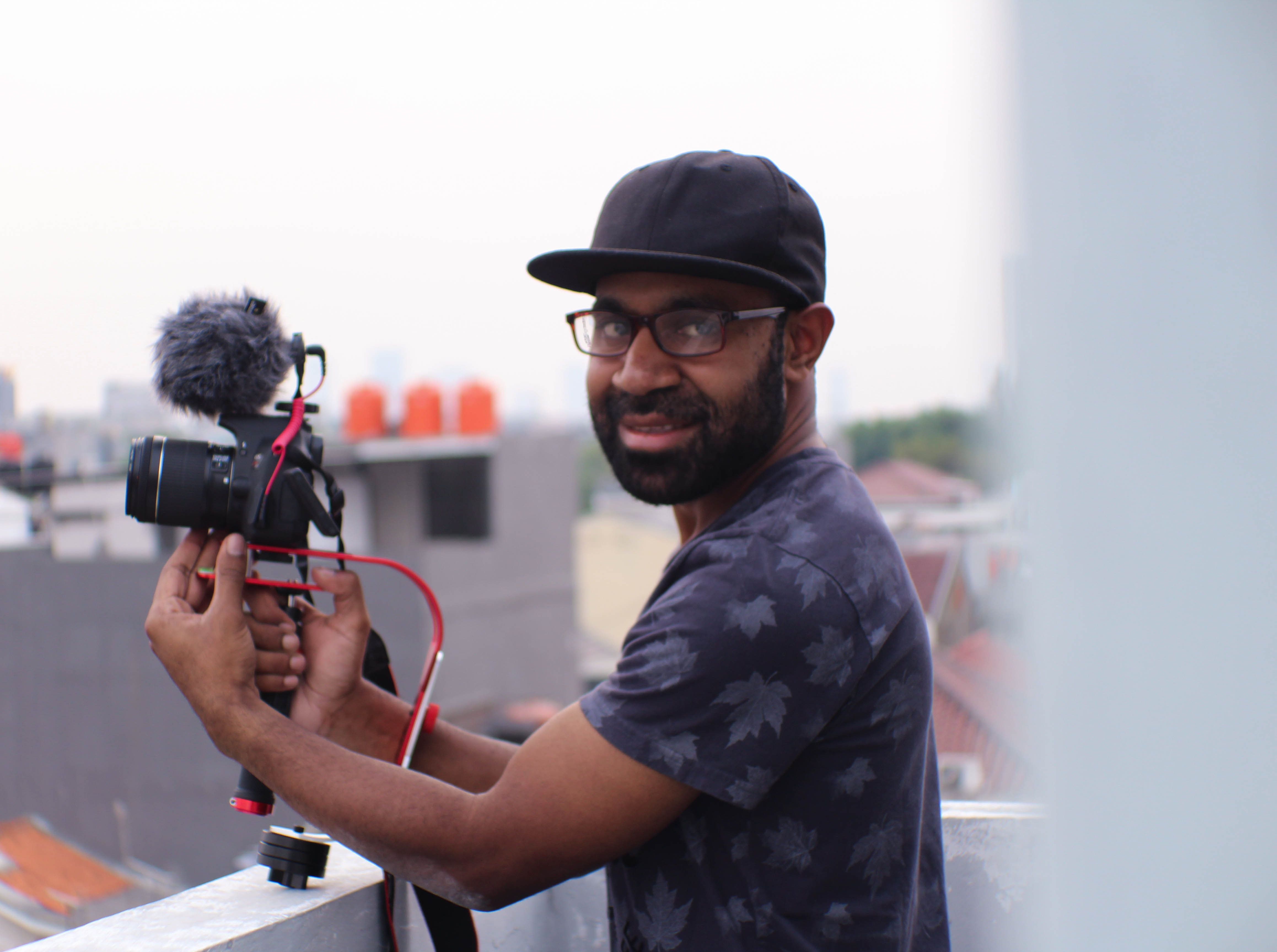 man holding camera beside terrace rail