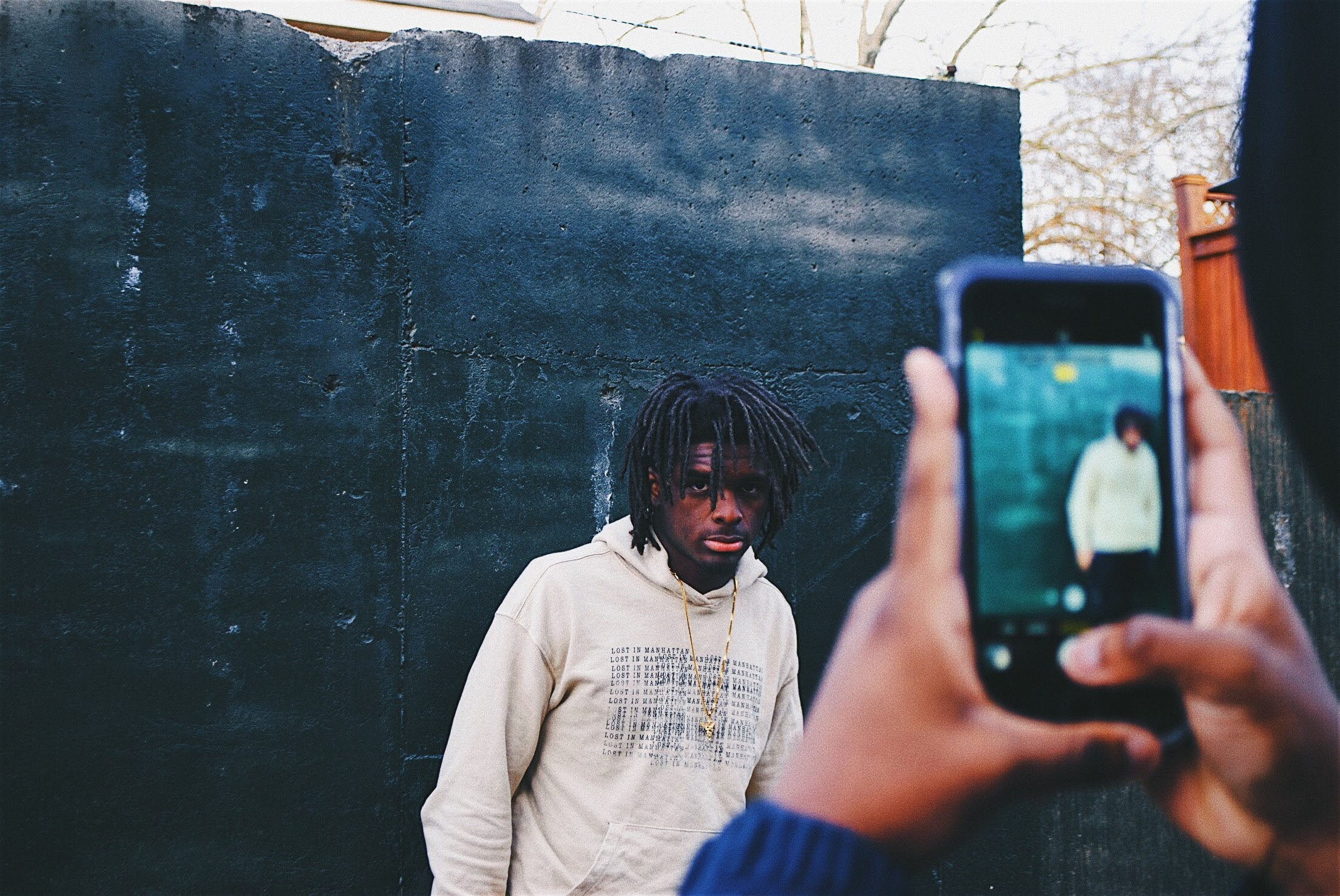 person taking picture of man wearing white pullover hoodie