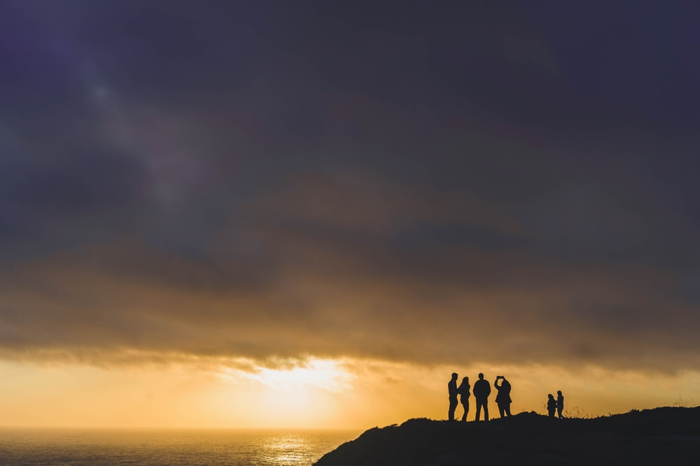 six people standing on mountain cliff at golden hour