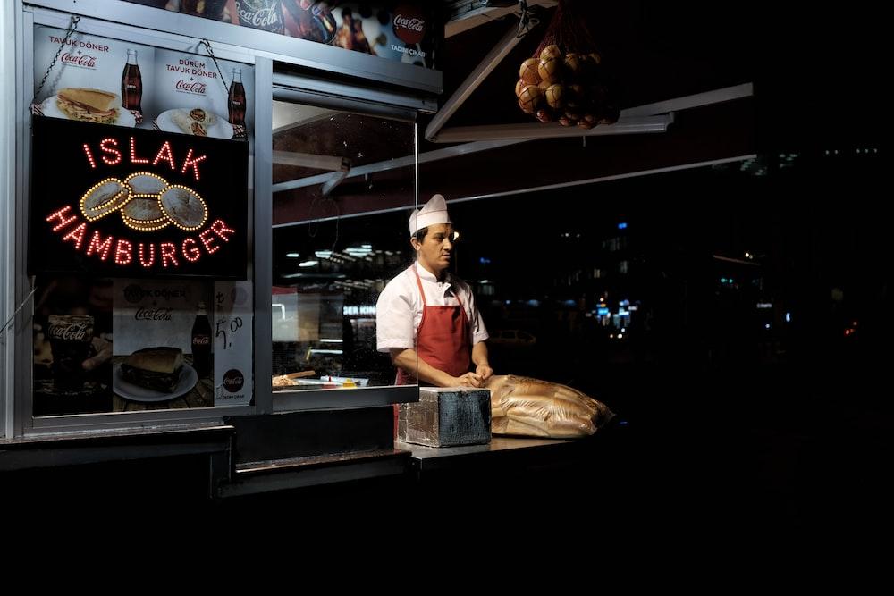 man standing on hamburger stall during night time