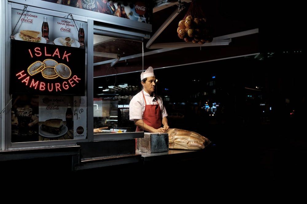 man standing on hamburger stall during night time