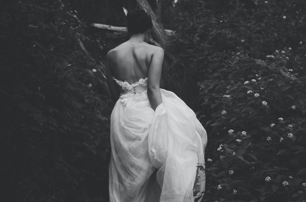 woman wearing gown between flowers