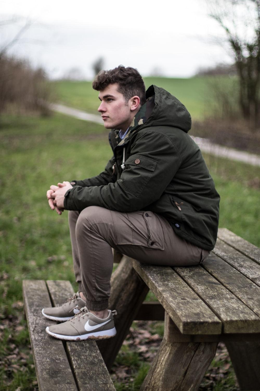 man sitting on brown wooden picnic bench during daytime
