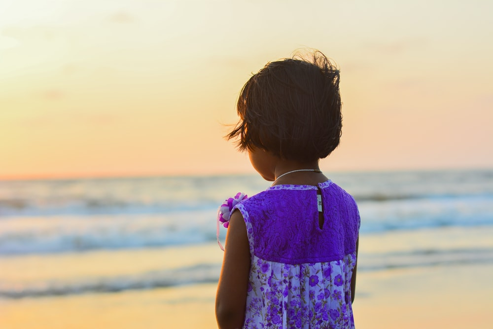 girl in white and purple dress standing on seashore facing the golden hour