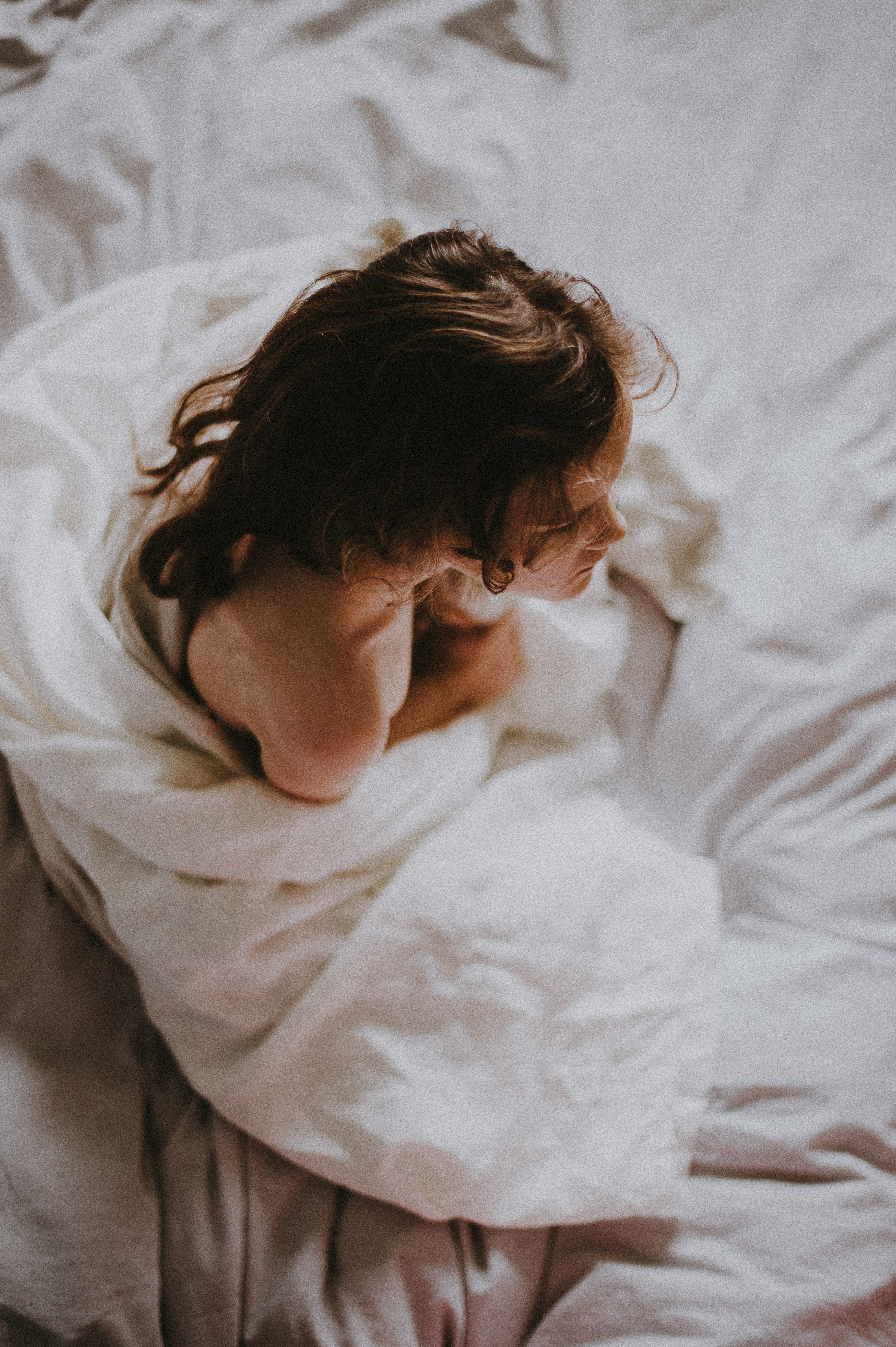woman sitting on bed covered with white blanket