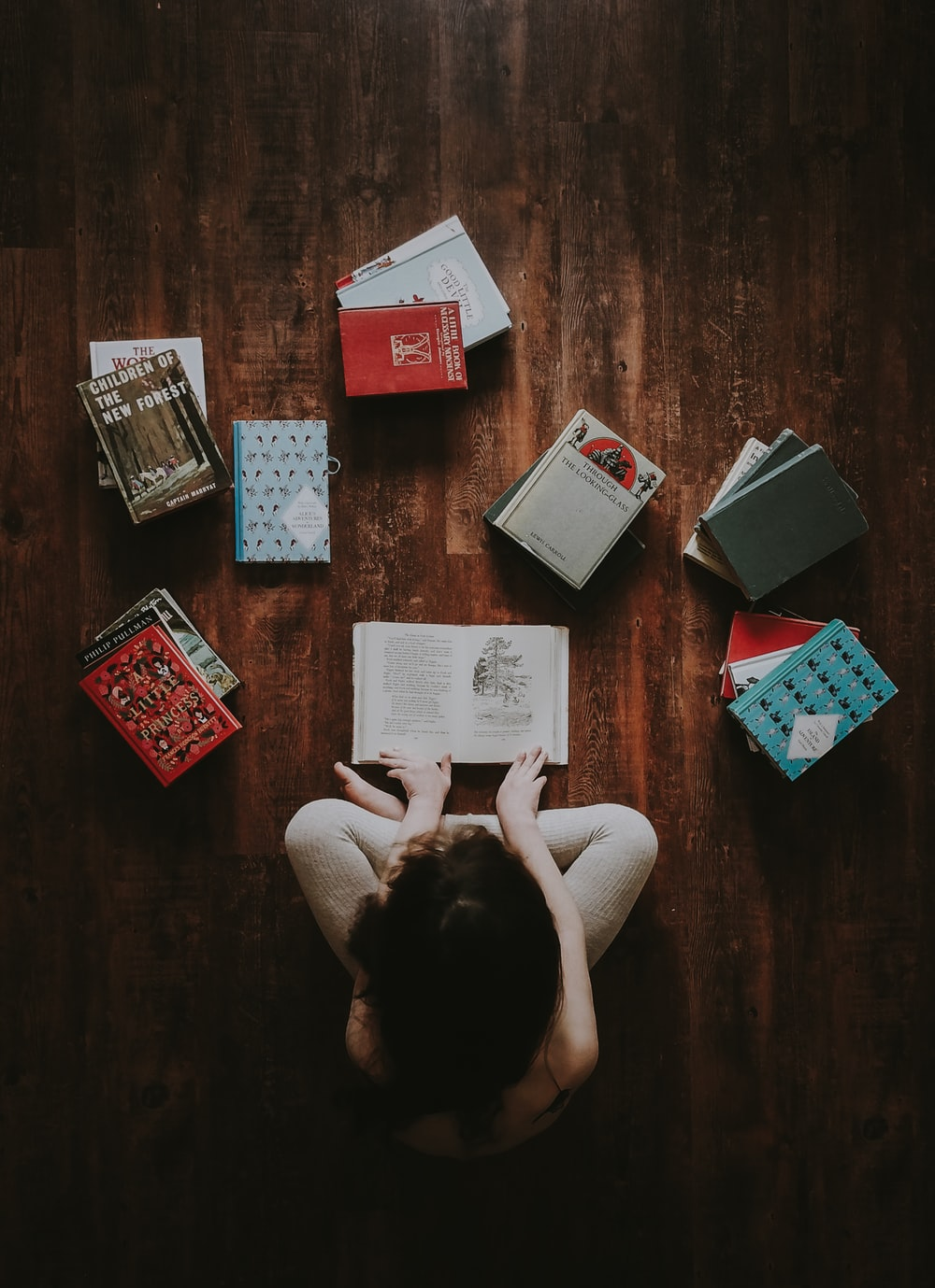 flat lay photography of woman sitting on brown wooden parquet flooring surrounded by books