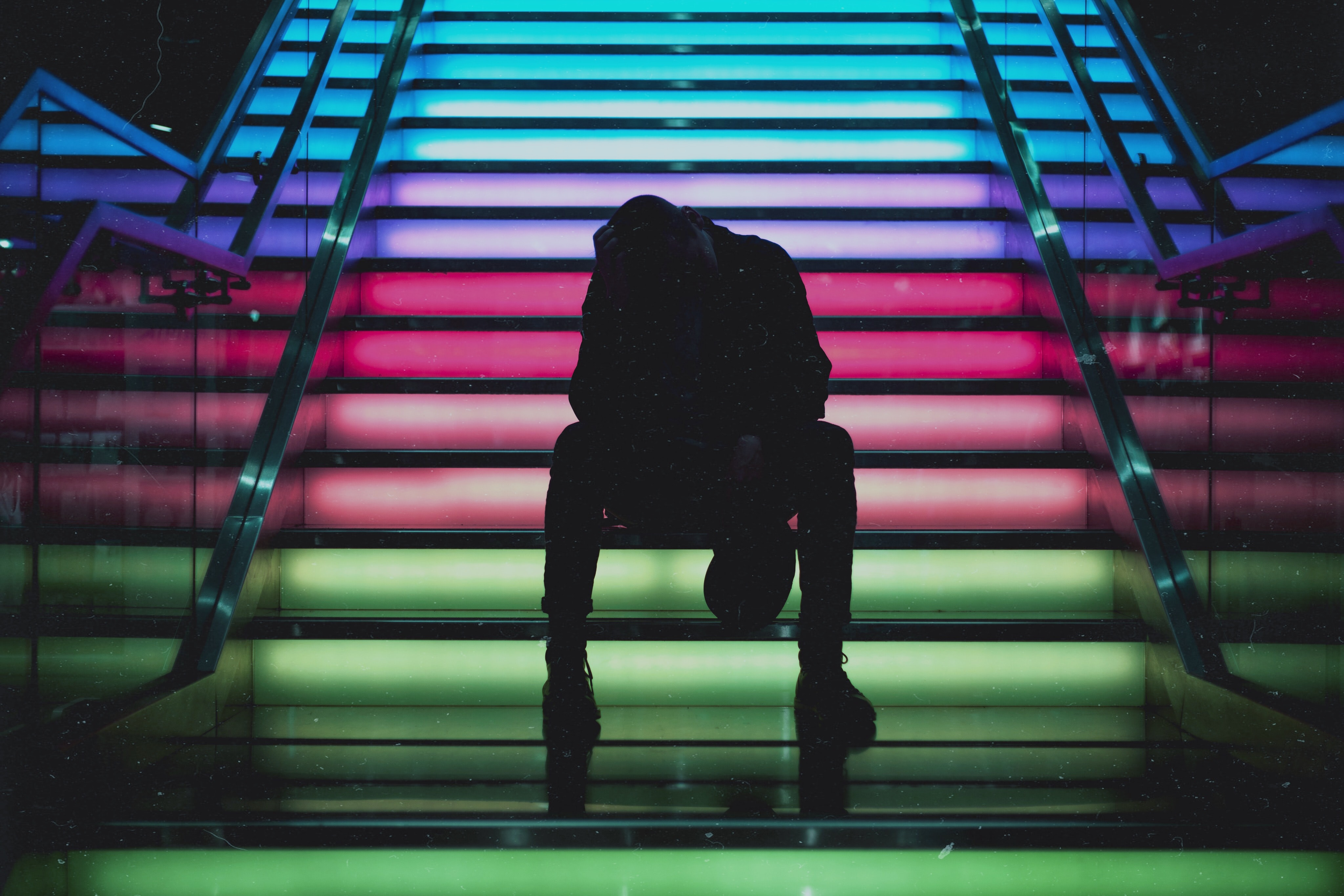 silhouette photo of man sittin on multicolored stair