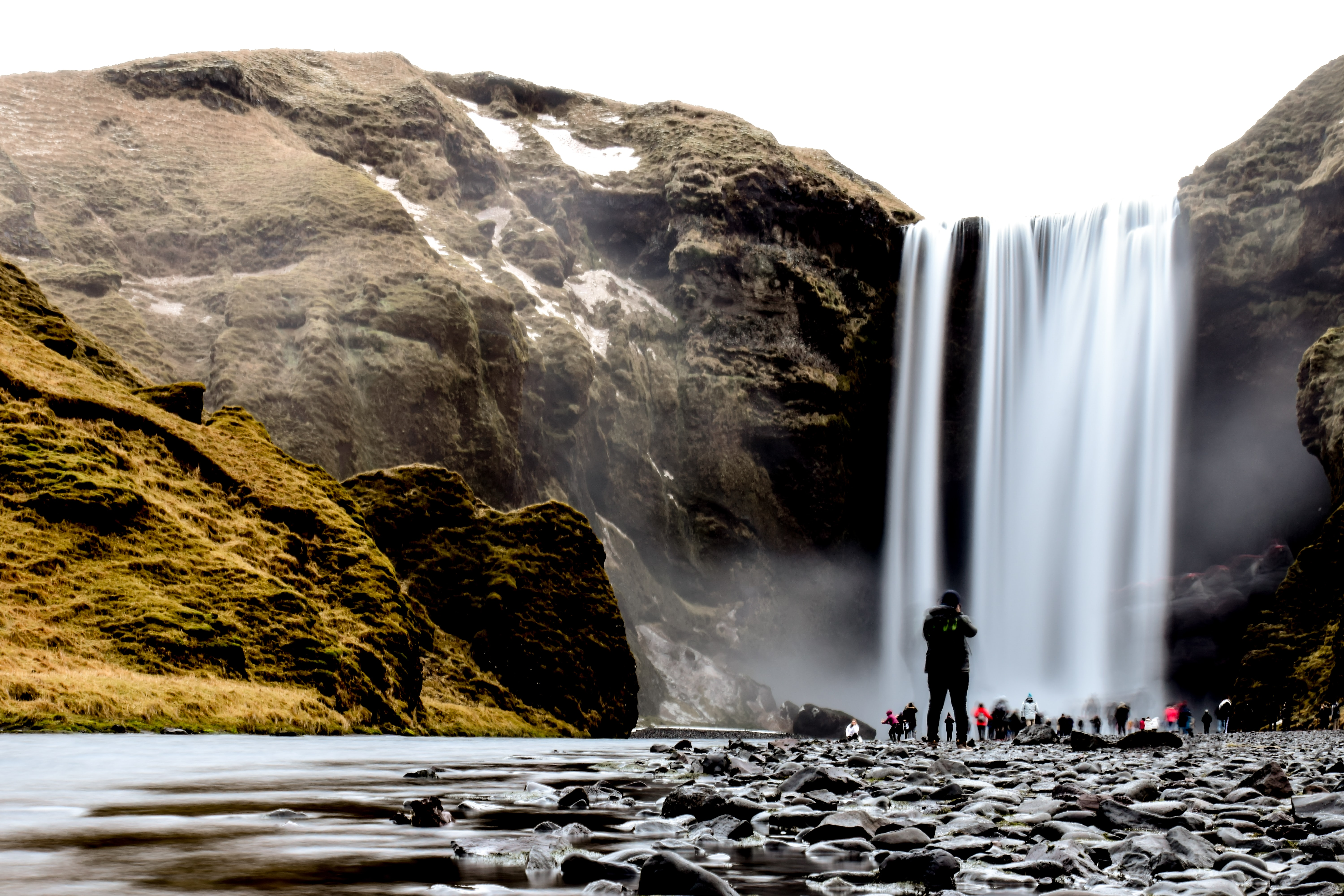 group of people standing near waterfalls