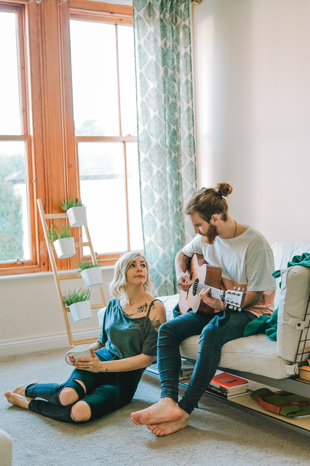 man sitting on sofa playing guitar looking at girl sitting on the ground near window inside room