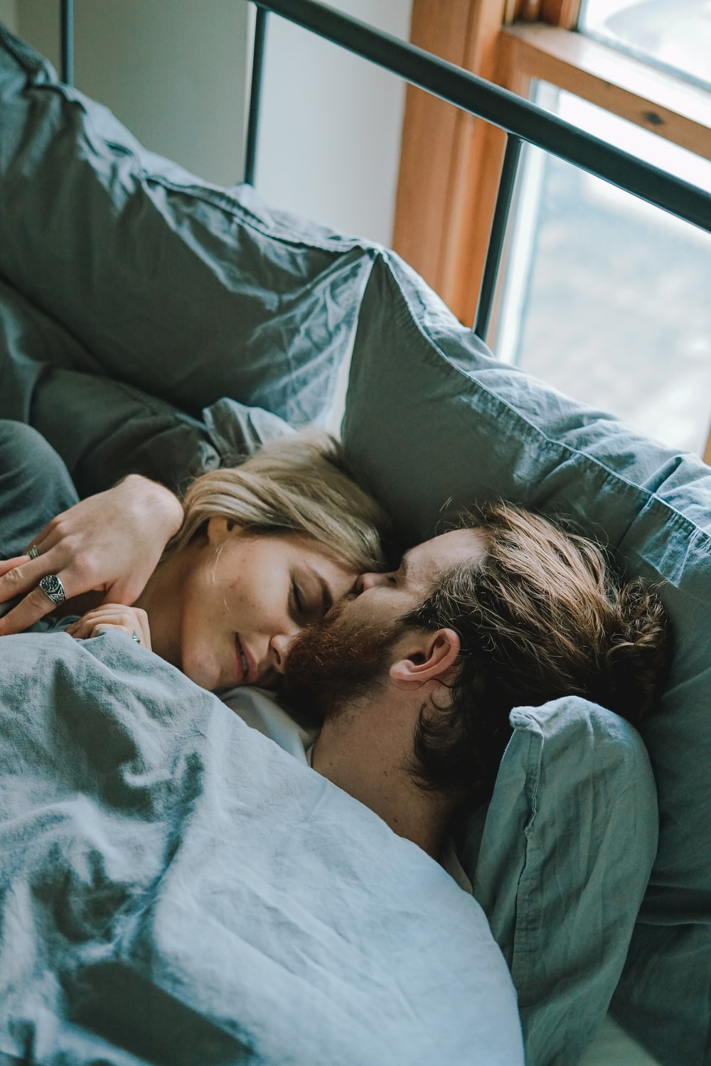 man kissing woman's forehead while lying on bed