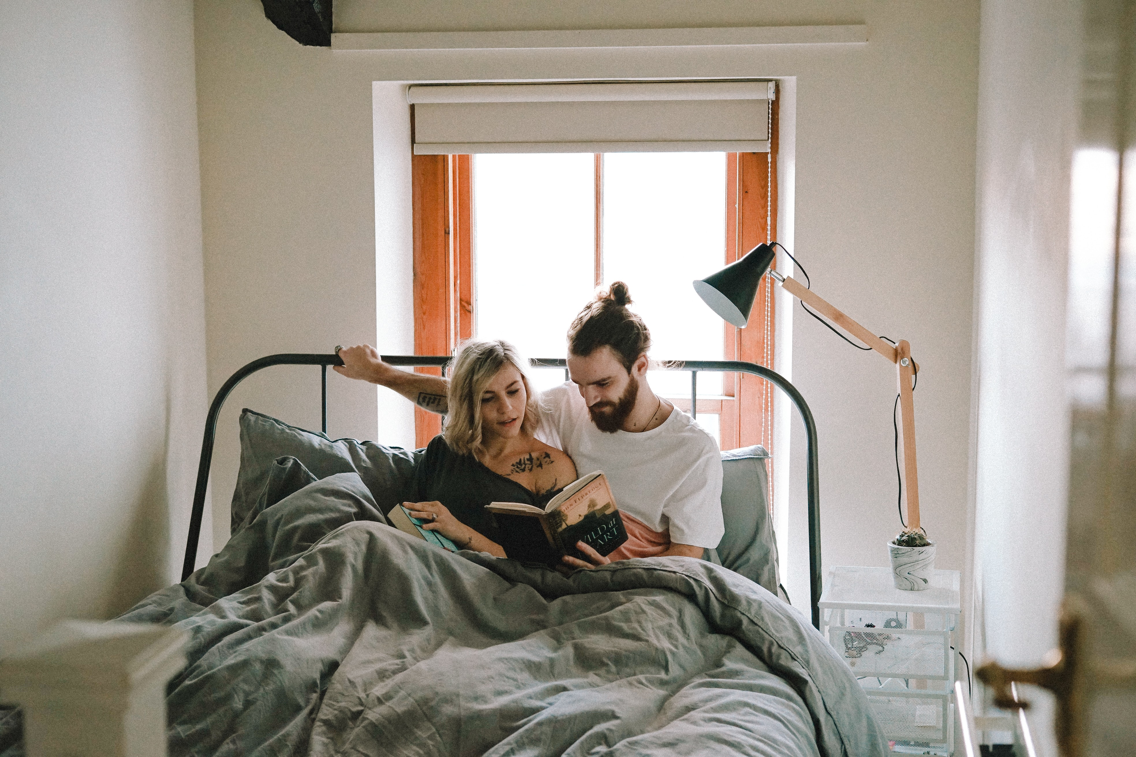 man and woman reading book on bed