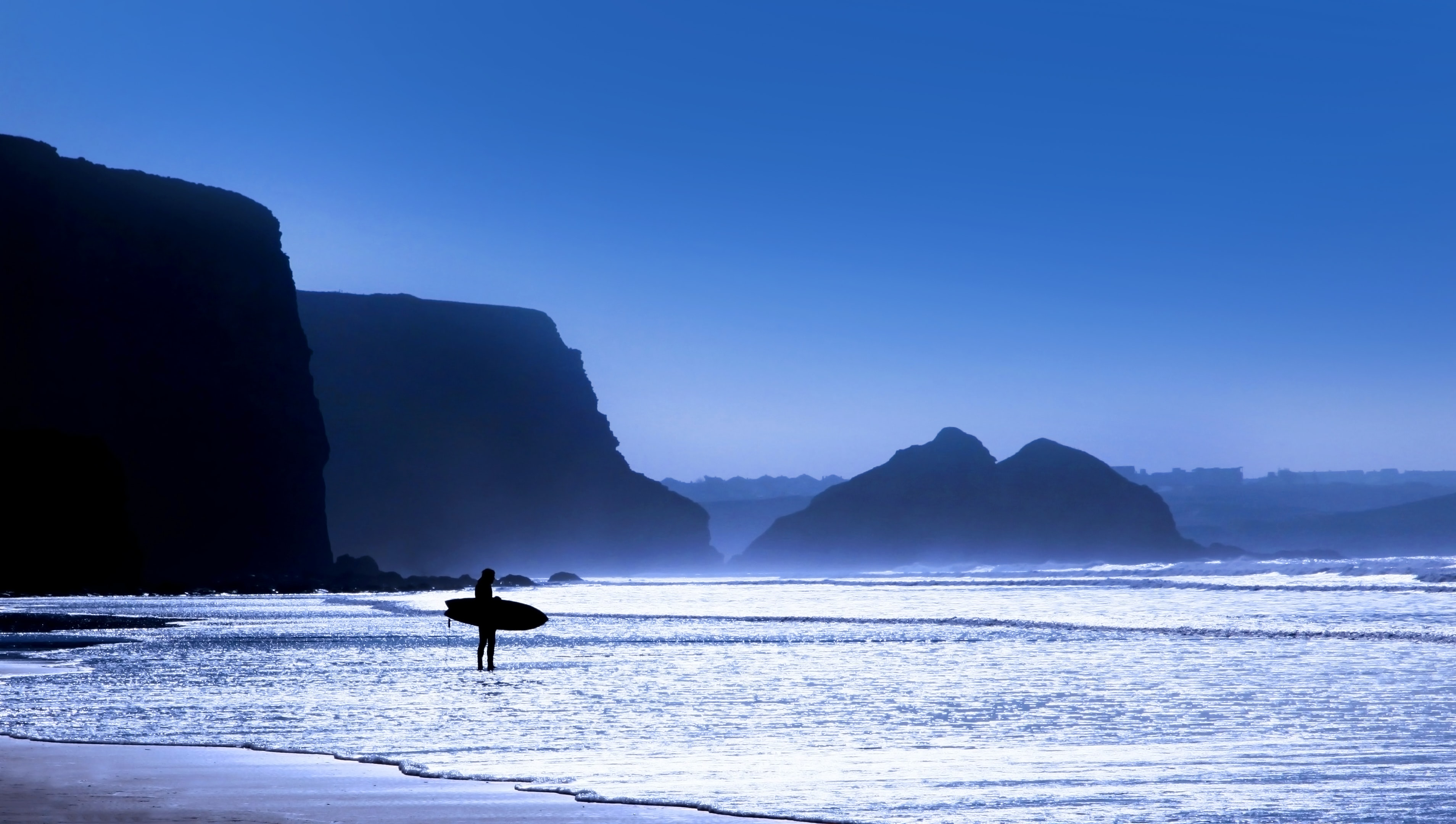 silhouette of person holding surfboard standing on seashore at blue hour