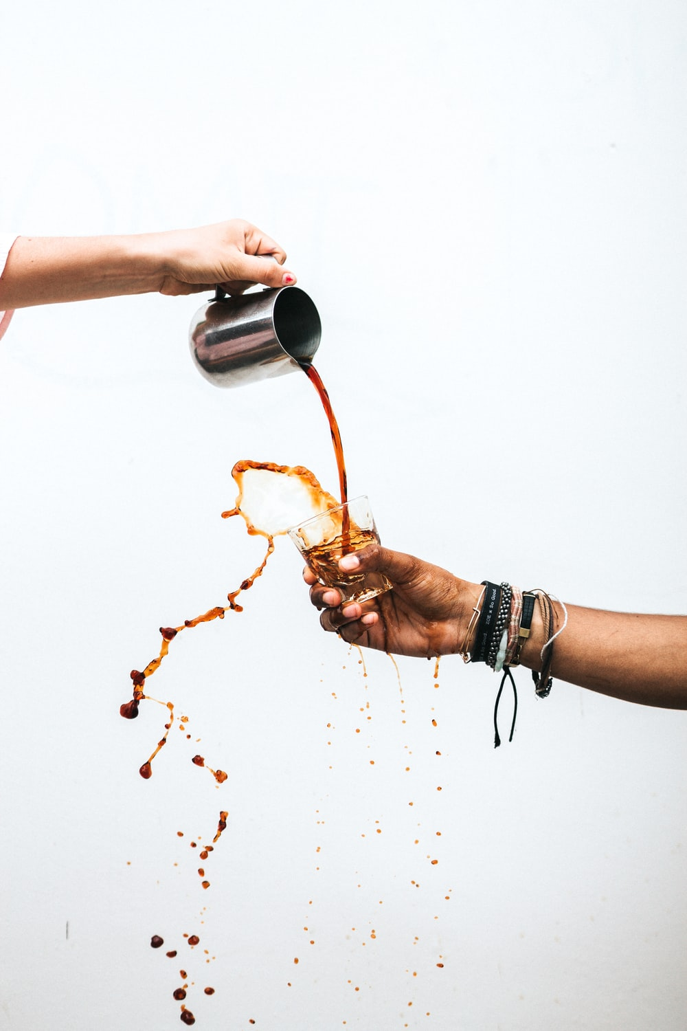 person pouring coffee into glass