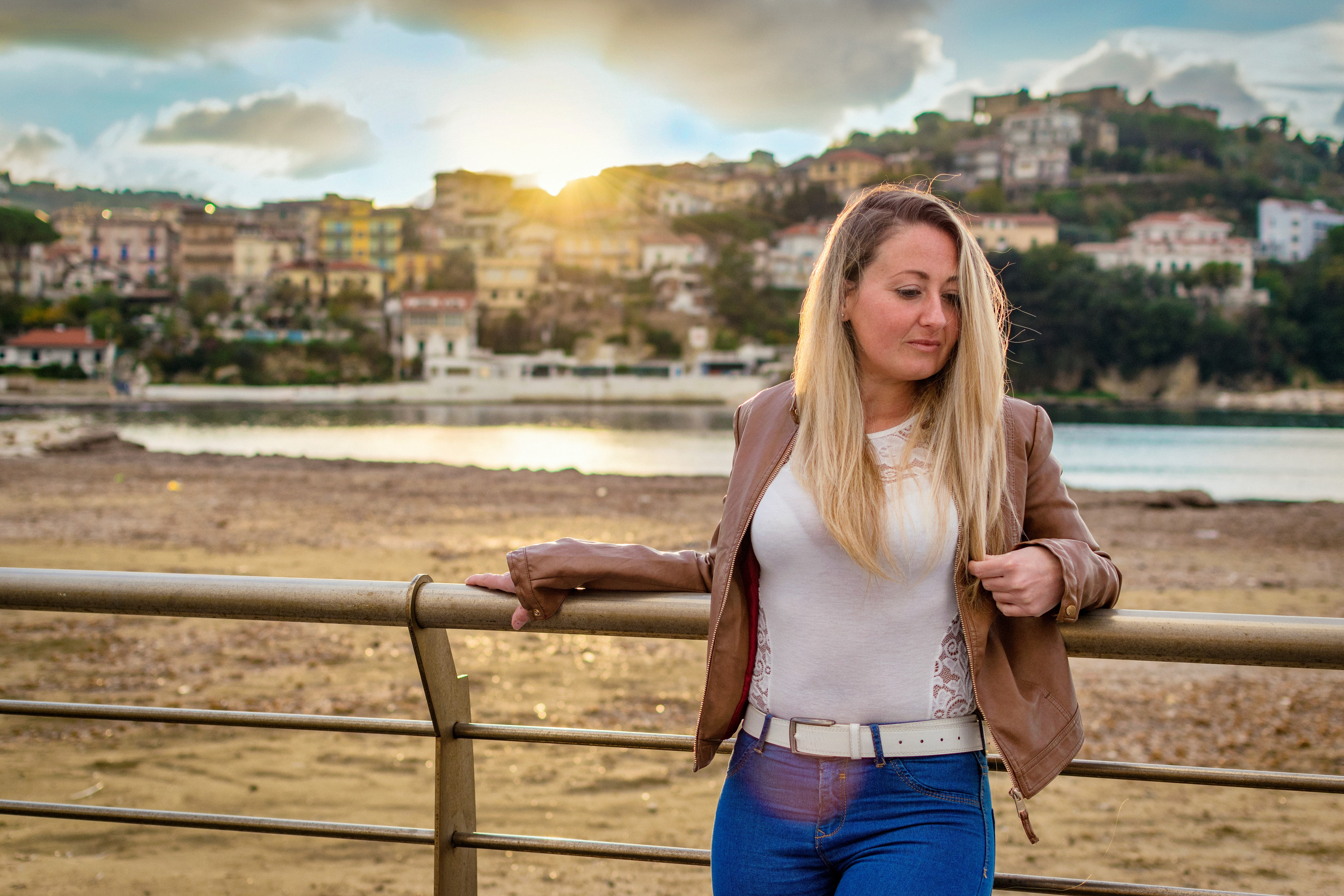woman leaning on bridge rail in front of buildings