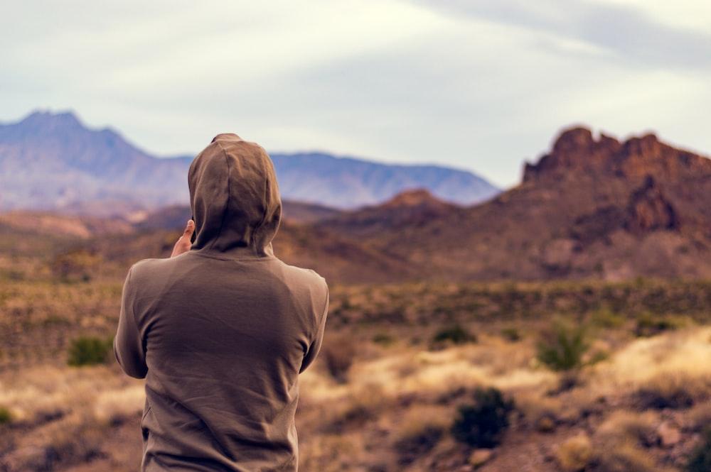 person wearing gray shirt facing jagged cliffs