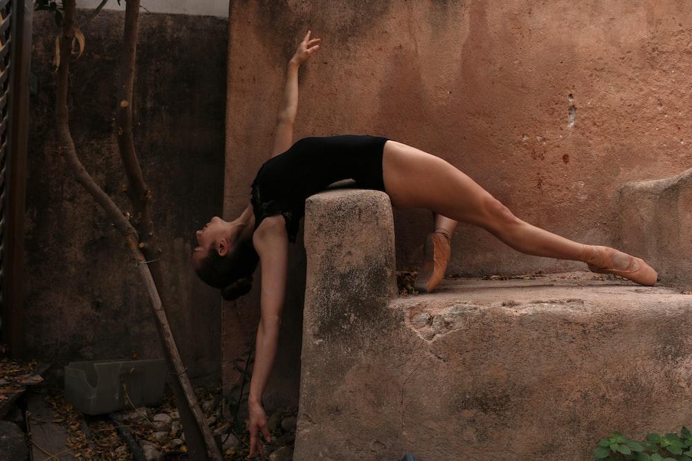 balerina woman lying on brown rock