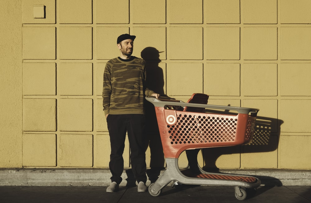 man standing near red and gray shopping cart
