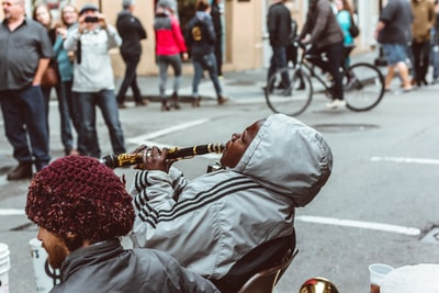 man sitting on chair playing flute new orleans zoom background