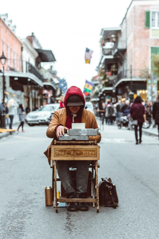 man sitting on table typing on typewriter
