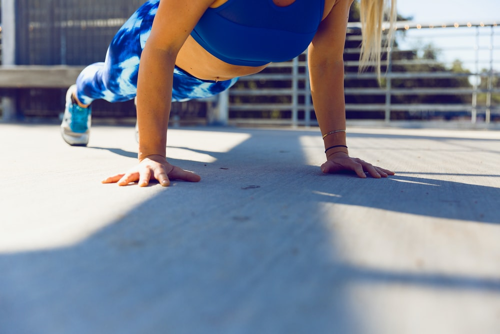 woman planking on gray asphalt road