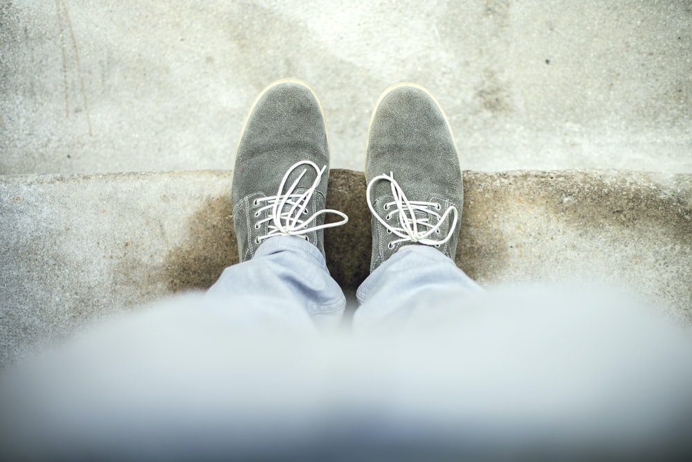 person taking a picture of gray shoes