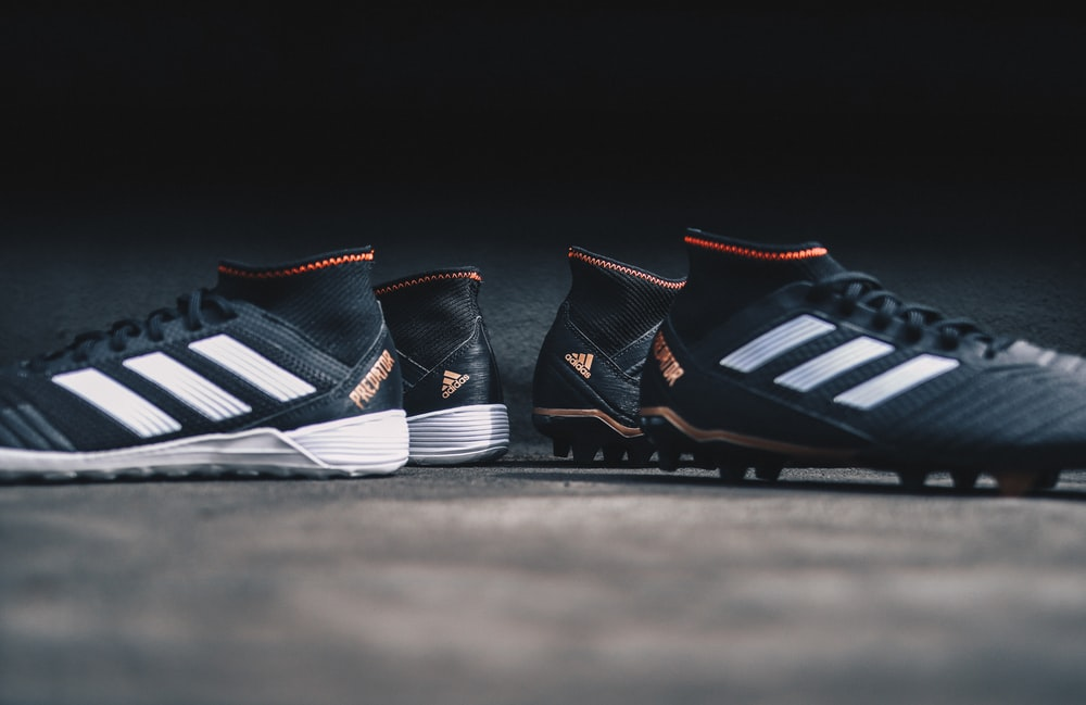 pair of black Adidas cleats