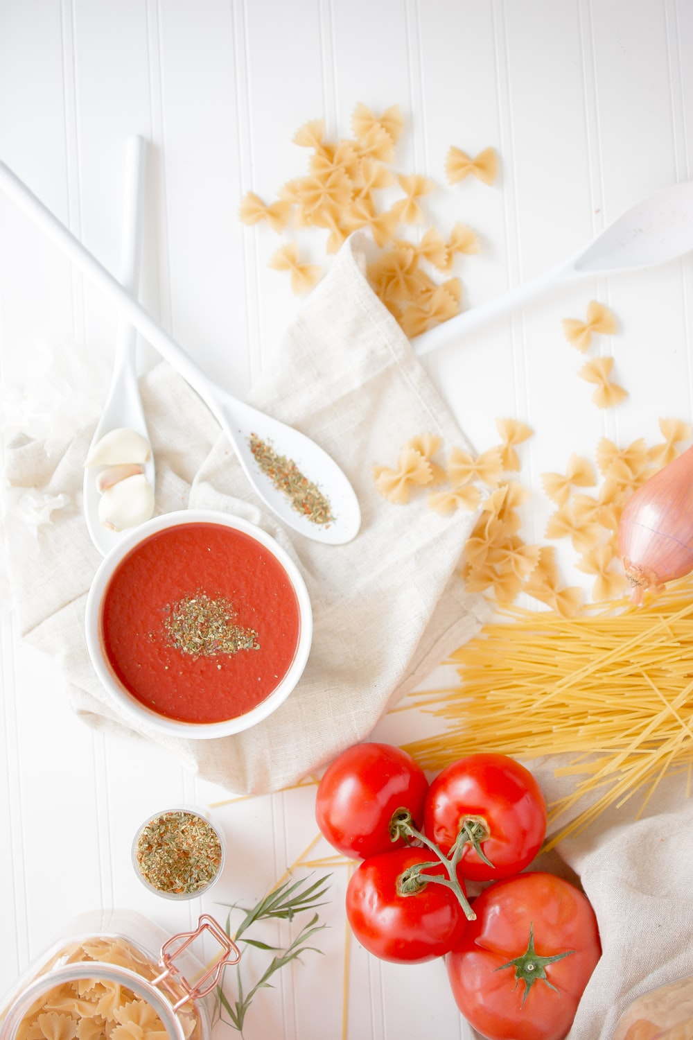 four red tomatoes beside pasta and bowl
