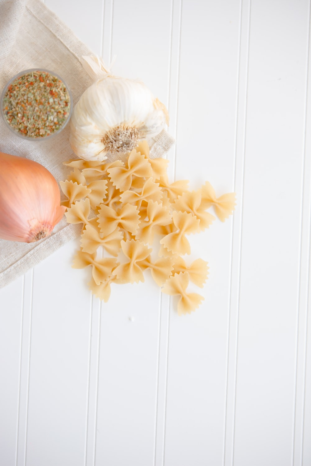 ribbon pasta beside garlic and onion