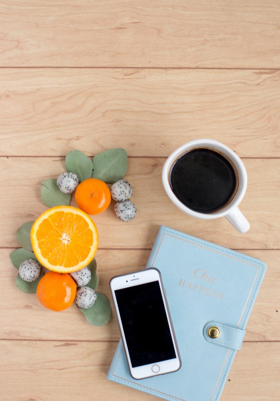 silver iPhone on book near coffee