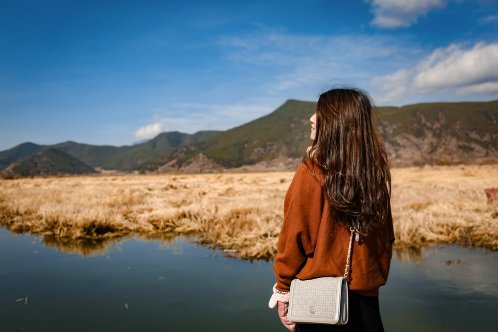 woman standing in front of green mountain under blue sky